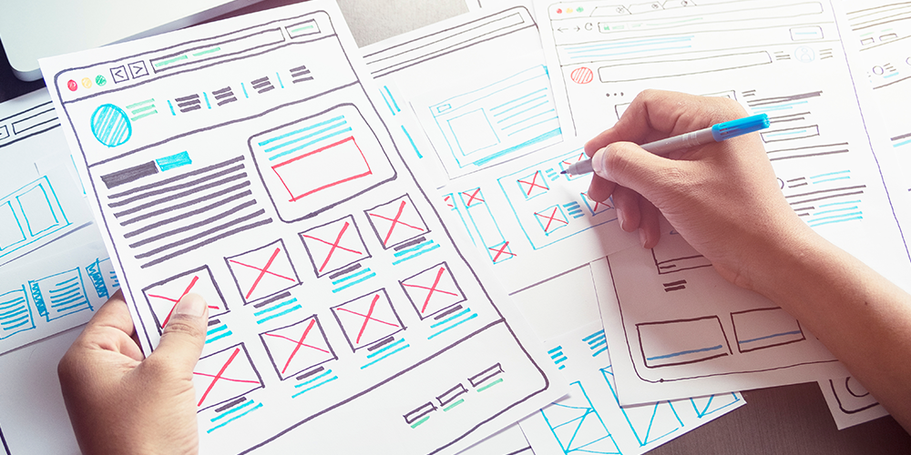 Graphic designer plans website design based on optimal user experience with pen and paper.
